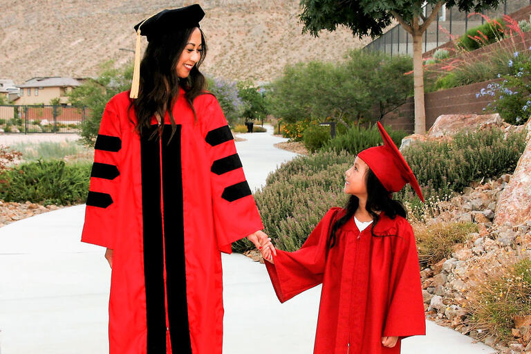woman and child each wearing a graduation gown