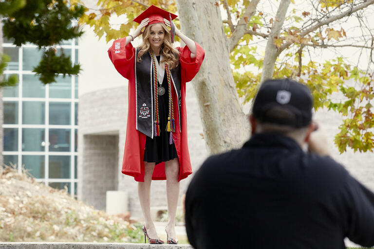 woman in commencement garb being photographed