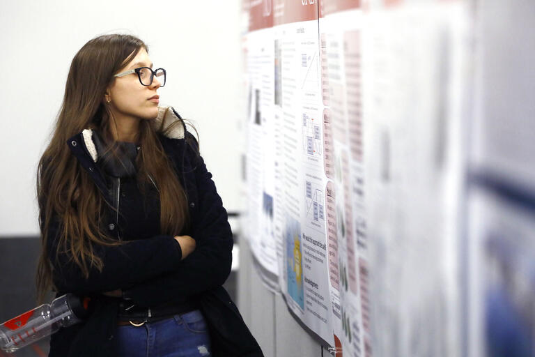 A female student wearing glasses looks at a poster describing a research project.