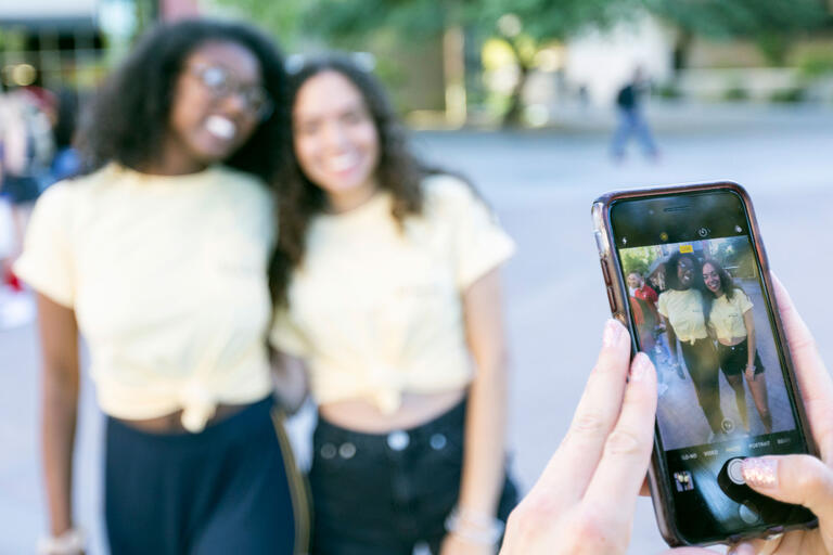 Two students pose for a photo wearing matching t-shirts while the camera focuses on a photo screen while the photo is being taken.
