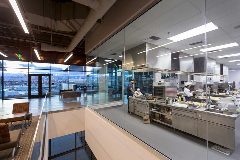 Students work in a test kitchen in front of a floor-to-ceiling windows with a view of Las Vegas at dusk.