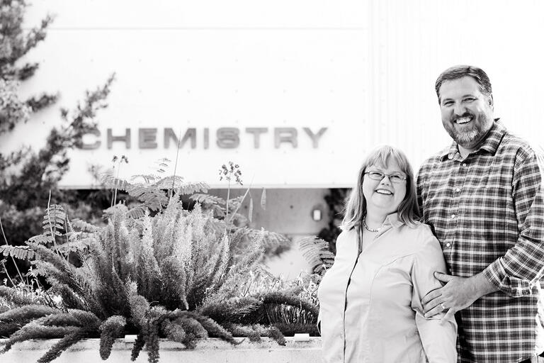 a woman and man stand near a cactus outside the chemistry building