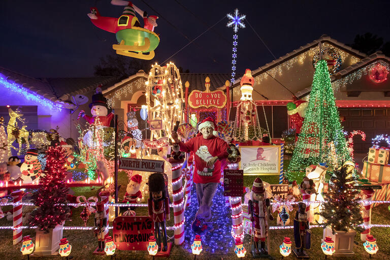 man standing outside house decorated with lights and holiday figures