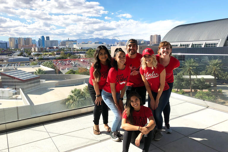 A group of six students wearing red tshirts stand on an outdoor patio with a view of Las Vegas in the background.