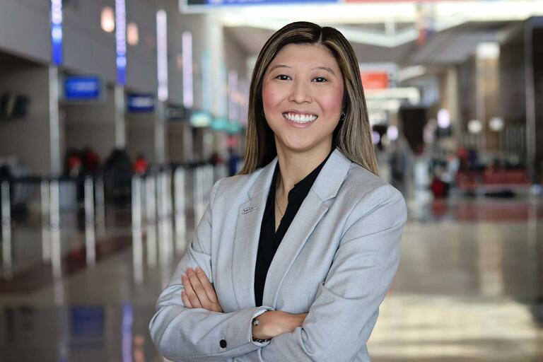 Kylies Fung stands in an airport.