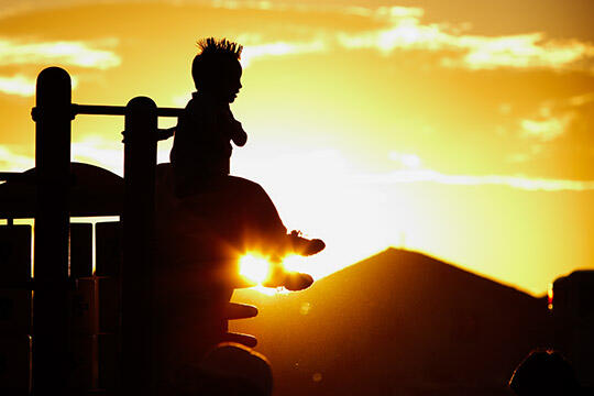 child plays on playground during sunset