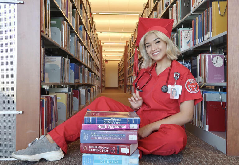maricel gomez wears red nursing scrubs as she sits on the library floor surrounded by books