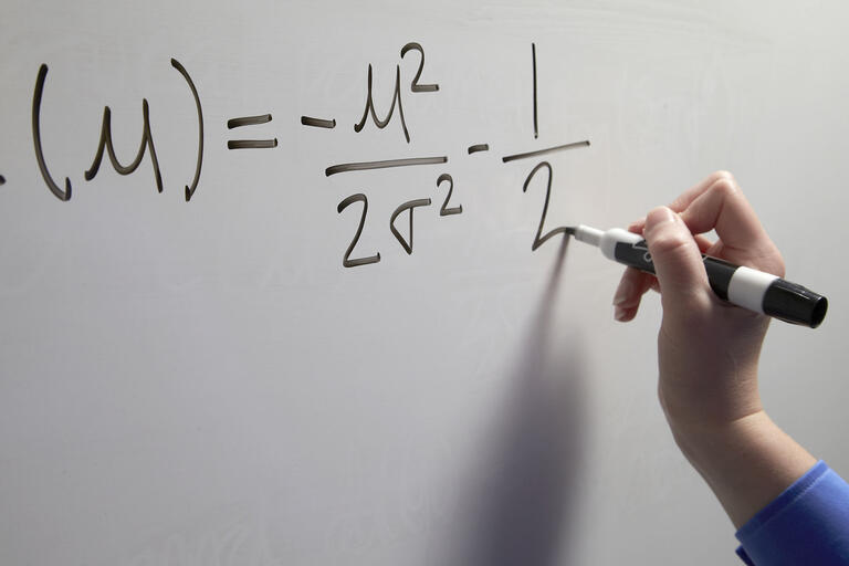 hand writing an equation on a whiteboard