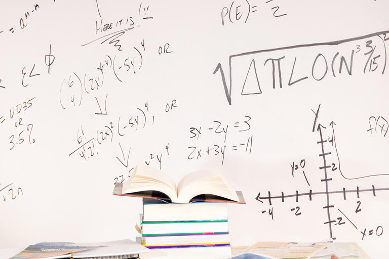 white board with math equations and books
