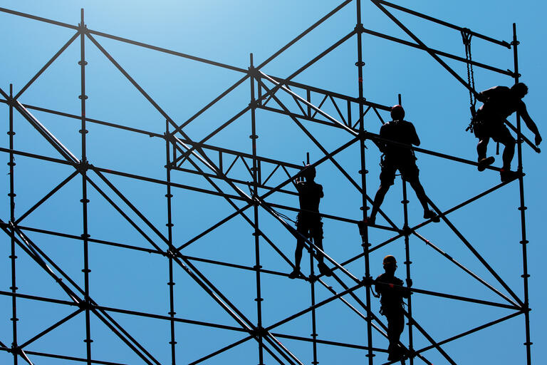 Workers set up scaffolding