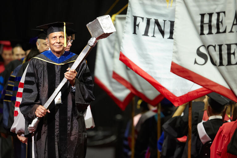 Sadanand Verma carries the university mace during commencement