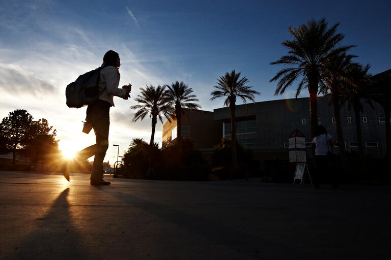 silhouette of student walking on campus during sunset