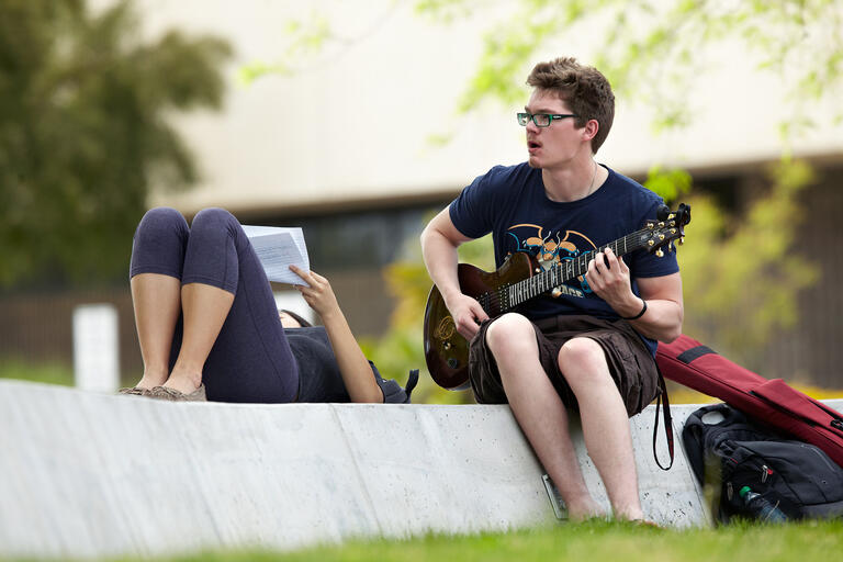 student plays guitar outside