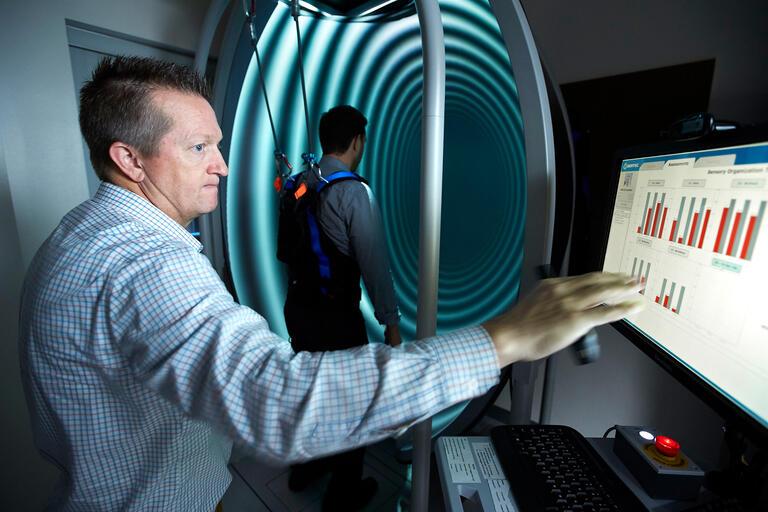 Merrill Landers works with balance testing equipment