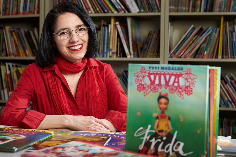 Denise Dávila sits at a table with children's books