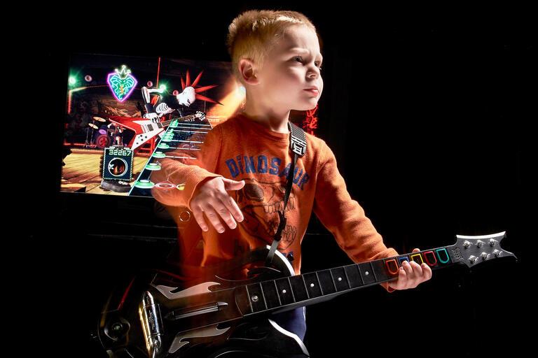 child plays guitar hero guitar