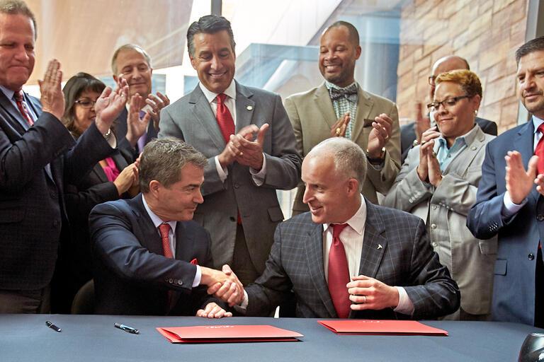 UNLV President Len Jessup, left, and Tesla Motors Vice President for Business Development Diarmuid O'Connell shake hands