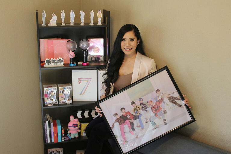 Nicole Santero at home, surrounded by BTS memorabilia, including a poster.