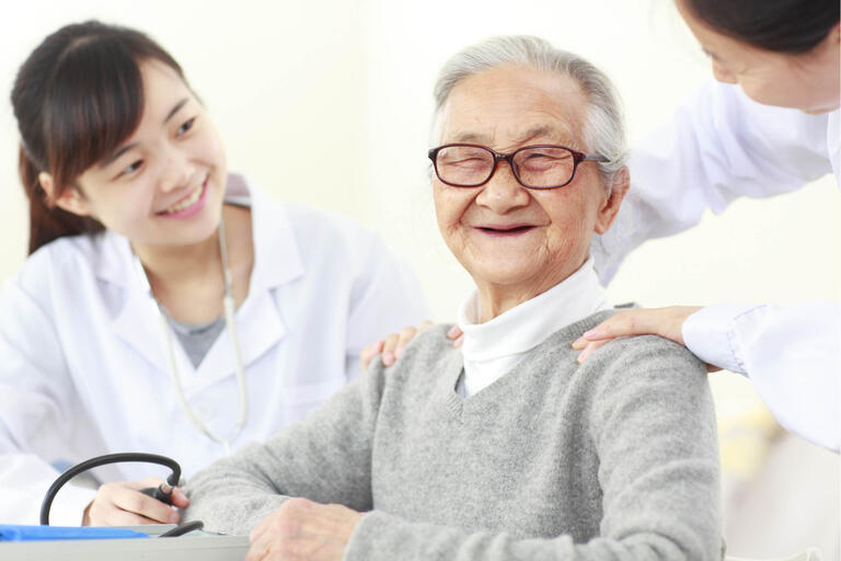 Asian elderly man with two medical providers
