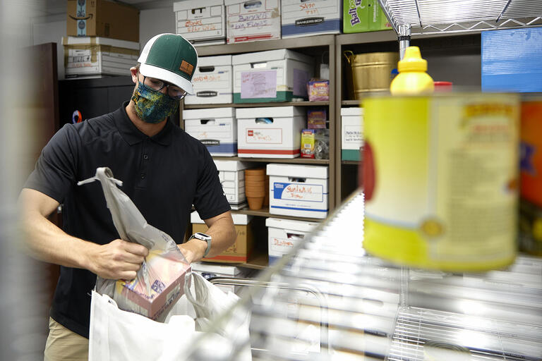 man wearing face mask working putting grocery items in bag in storeroom