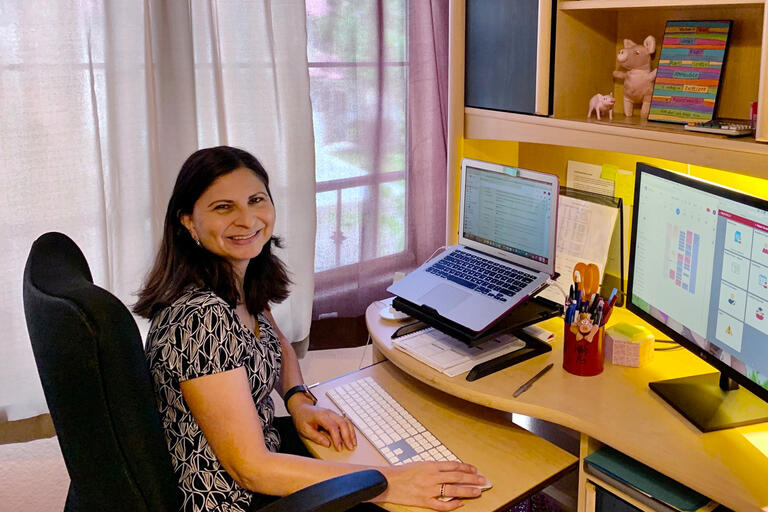 Debbie Pattni seated in front of a computer in her home office.