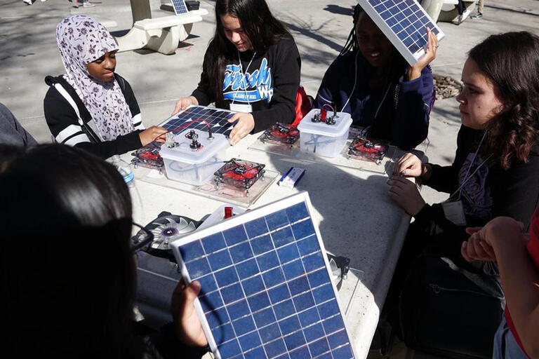 young women looking at solar components