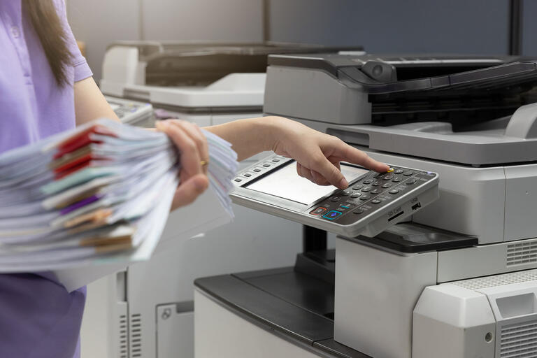 woman at copier with stack of papers