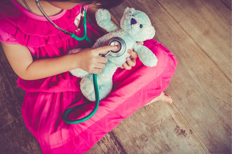 A girl holds a stethoscope to a teddy bear