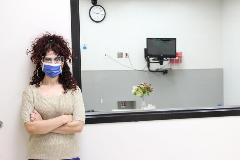 woman in mask outside an medical exam room