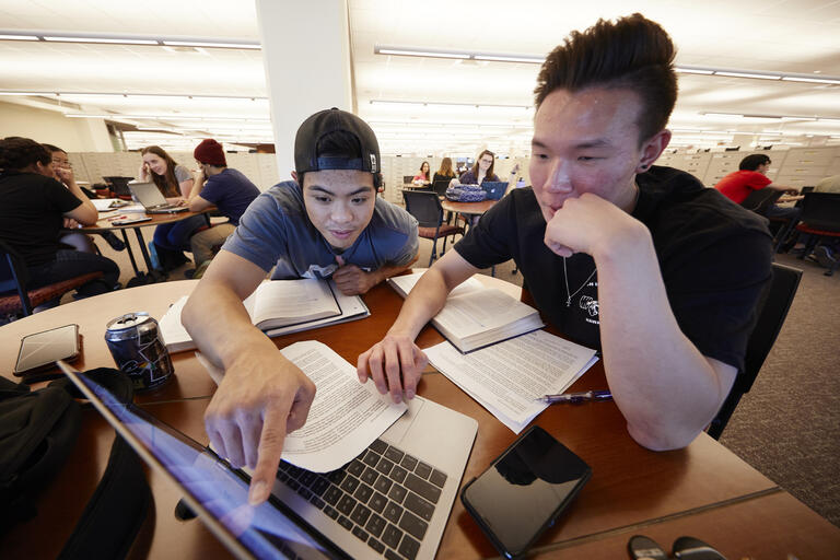 two students working in front of laptop