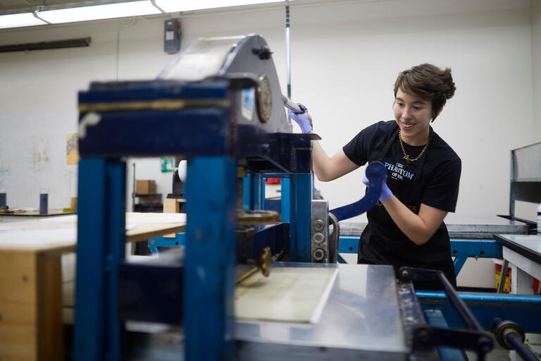 A student uses printing equipment in an art studio.