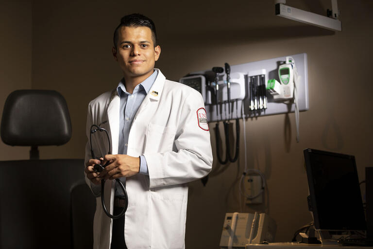 Student in white medical coat stands in front of medical equipment