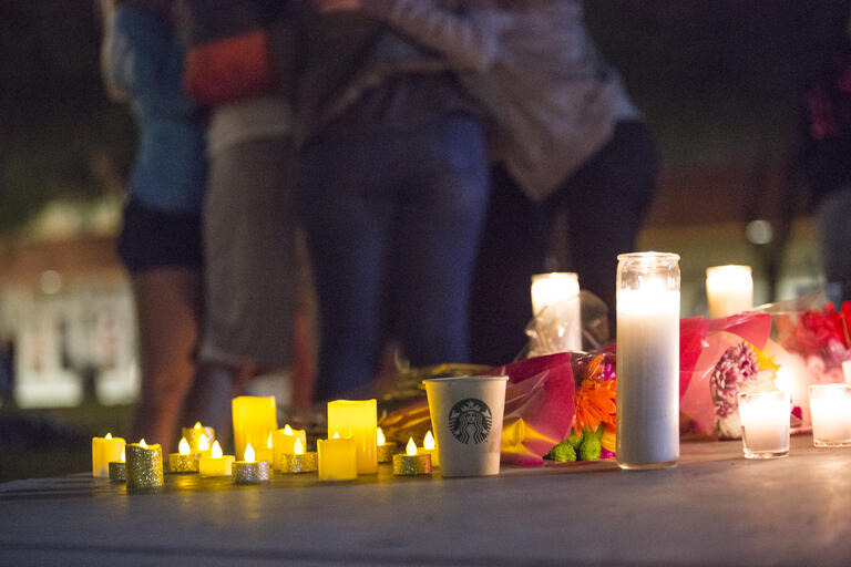 candles in forground, group hugging in background