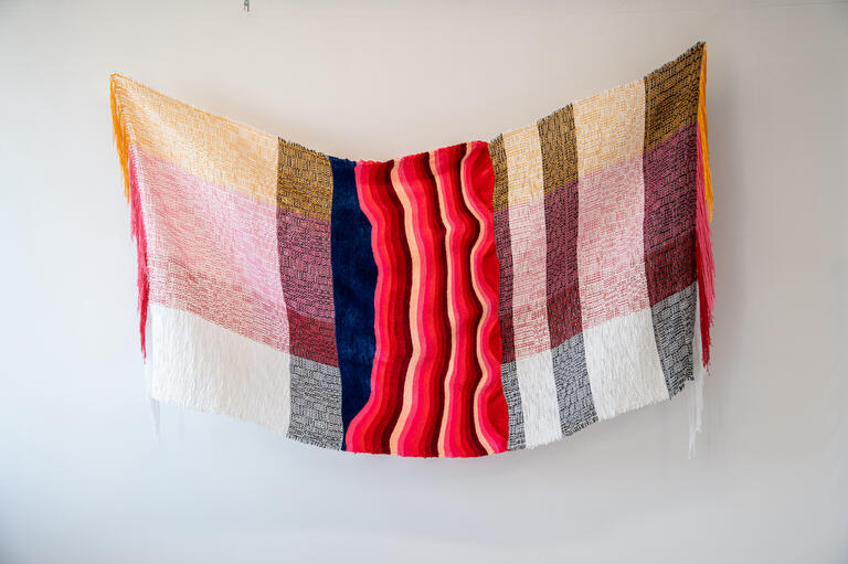 A art piece of fabric hanging from the wall.