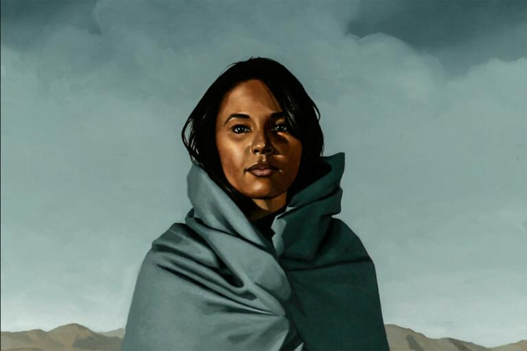 Artwork of a woman wrapped in a colorful robe on a desert landscape with mountains in the distance behind her.