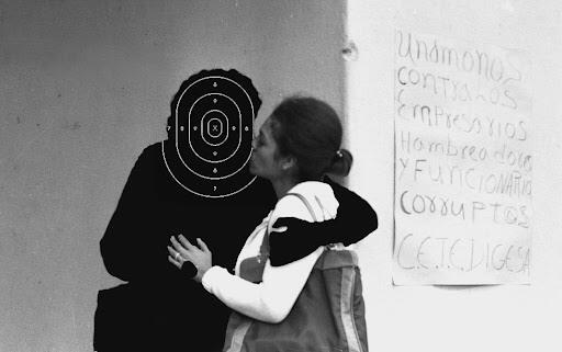 A black and white photograph of two people embracing. The photograph has been altered so that one figure is blacked out.