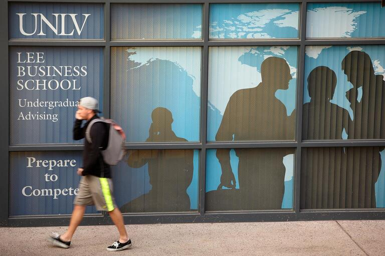 Student walking in front of a building with Lee Business School sign on the windows.