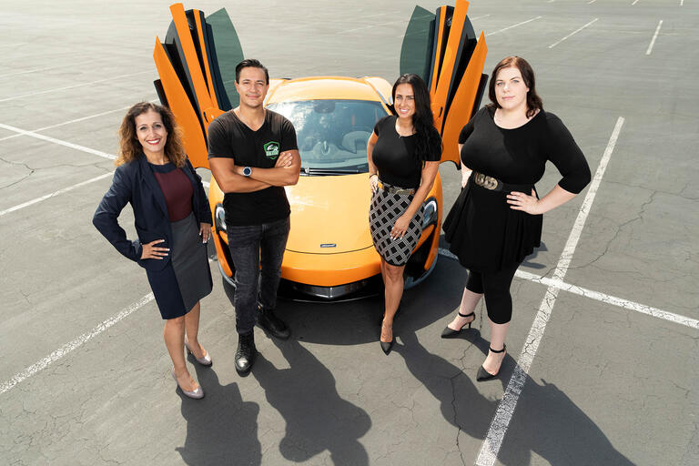 Professor Anjala Krishen, business owner Serge Shaakov, and students Magdalena Kobylak and Emma Glaze stand in front of a yellow car.