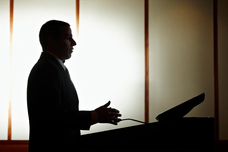 silhouette of man speaking at a podium