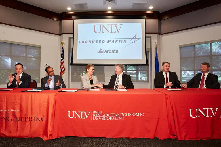 Members of UNLV and Teledyne Brown Engineering shake hands during a signing ceremony