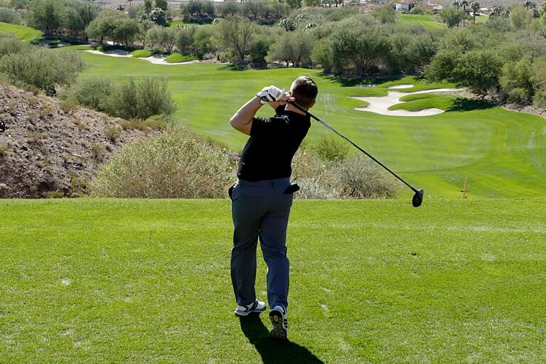 A golfer swings club