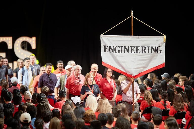 College of Engineering sign being held during a procession at a student event.