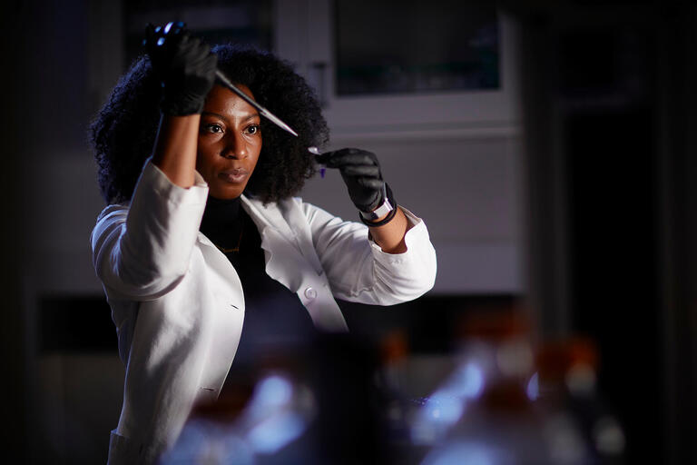 Female in a lab coat holding a syringe