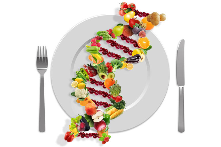 dna strand made of veggies atop a dinner plate with silverware at sides