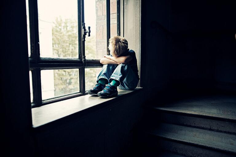 Boy sitting on a windowsill with his head buried in his arms