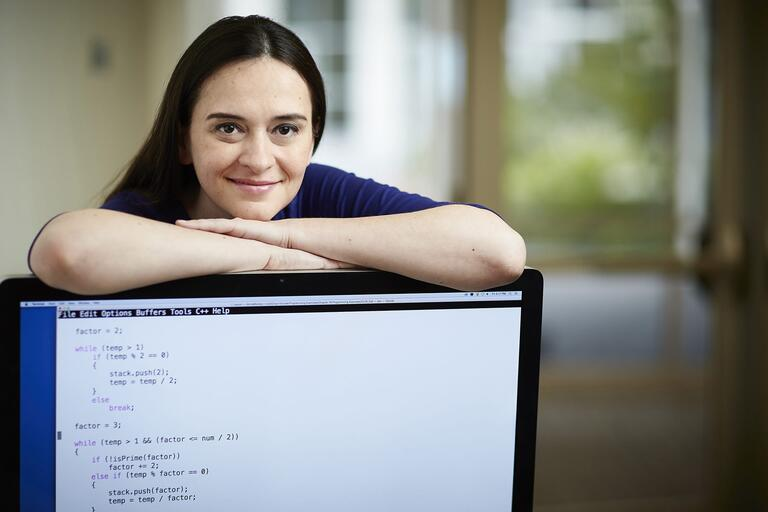 Fatma Nasoz with her arms on top of a computer screen that id displaying code.