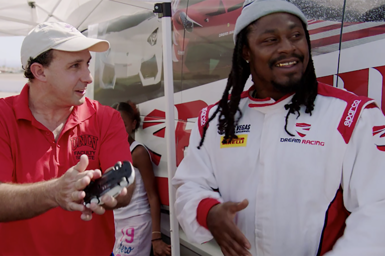 Professor Michael Pravica, left, explains the physics of auto racing to Oakland Raiders running back Marshawn Lynch.