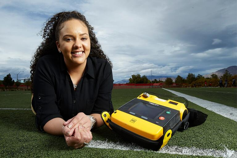 Chely Arias laying on a field next to a defibrillator