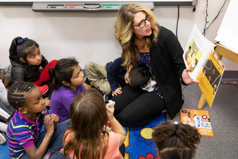 A teacher reads a book to young children, while they are all sitting on the floor.