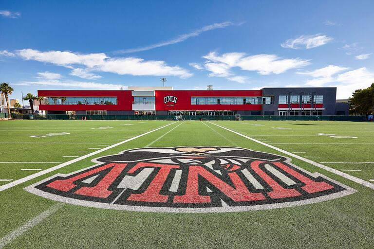 Fertitta football complex with the UNLV logo painted on the football field in front of teh complex.